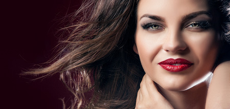 Beauty closeup portrait of attractive elegant brunette woman with red lips and long hair. Perfect makeup. Wind in hair.Girl with beautiful smile.
