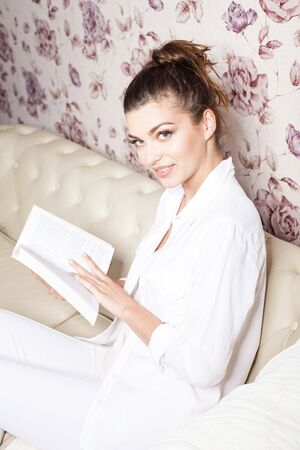 Young beautiful smiling brunette woman reading book at home, sitting on the sofa. photo