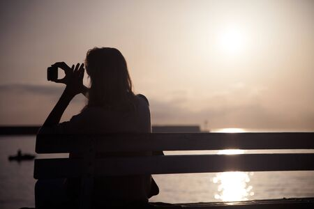 Young woman taking photos of beautiful sunrise over the sea. Outdoor shot. photo