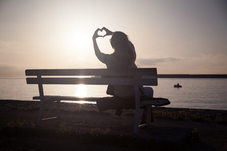 Beautiful young woman looking at amazing sunrise, showing heart symbol. Summer photo.