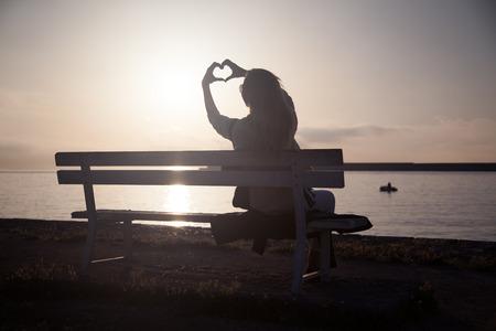 Schöne junge Frau, die erstaunliche Sonnenaufgang, mit Herz-Symbol. Sommer-Foto.