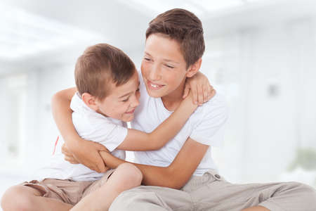 Two brothers posing at home, hugging. Family portrait.