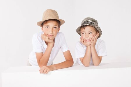 family portrait: Two brothers posing in studio wearing fashionable hat, smiling. Family portrait. Stock Photo