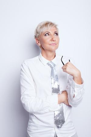 secretaria sexy: Beautiful confident blonde businesswoman holding eyeglasses, posing in studio.