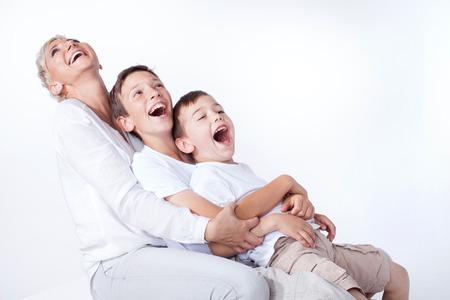 familia abrazo: Foto de familia. Madre hermosa rubia posando con dos chicos jóvenes, sonriendo. Foto de archivo