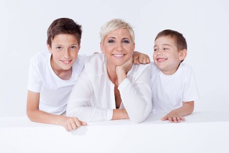 stylish man: Family photo. Beautiful blonde mother posing with two young boys, looking at camera. Stock Photo