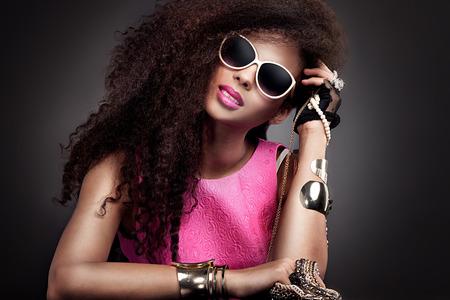 mujer sexy: Chica de belleza de moda posando en gafas de sol. Joyer�a de la mujer que sostiene joven atractiva. Chica con el pelo largo sano.