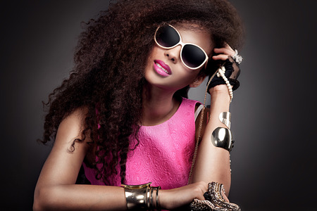 Fashion beauty girl posing in sunglasses. Sexy young woman holding jewelry. Girl with long healthy hair.