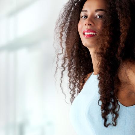 capelli lunghissimi: Foto di moda della bella ragazza sorridente in abito blu. Donna con capelli ricci lunghi.
