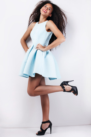 Fashion photo of beautiful smiling young girl in blue dress. Woman with long curly hair.
