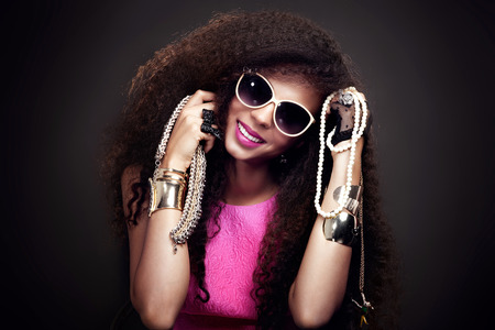 long hair: Fashion beauty girl posing in sunglasses. Sexy young woman holding jewelry. Girl with long healthy hair.
