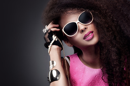 dark brown hair: Fashion beauty girl posing in sunglasses. Sexy young woman holding jewelry. Girl with long healthy hair.