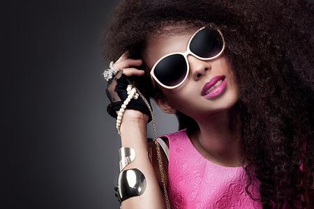 capelli lunghi: Moda bellezza ragazza in posa in occhiali da sole. Sexy giovane donna in possesso di gioielli. La ragazza con i capelli lunghi sani. Archivio Fotografico