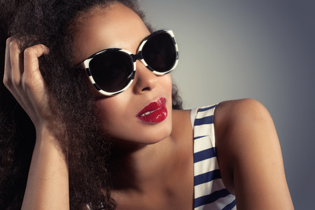 Closeup beauty portrait of young attractive woman wearing fashionable sunglasses. African american girl with red lips.