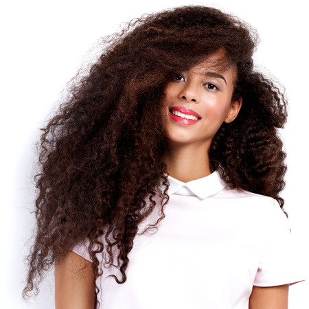 Beautiful young african american woman with long healthy hair posing in studio wearing fashionable dress. Girl with perfect delicate makeup. Indoor shot.
