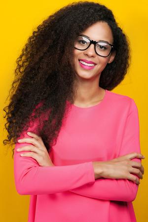 Schöne junge glückliche Afroamerikanerfrau mit erstaunlichen Offenes Lächeln. Mädchen, das Kamera, trägt Brille. Mädchen mit den langen lockigen Haaren gesund. Studio shot.