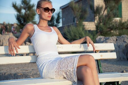 luxury lifestyle: Elegant beautiful woman sitting on white bench, relaxing. Summer time. Outdoor photo. Stock Photo