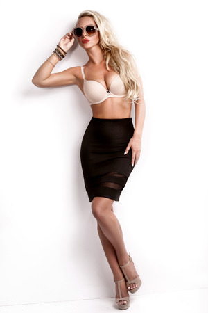 modelos desnudas: Sexy hermosa mujer posando rubio, vestido con elegante falda y la ropa interior y gafas de sol de moda. Chica con el pelo largo. Perfect cuerpo delgado.
