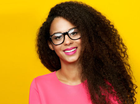 Beautiful young happy african american woman with amazing toothy smile. Girl looking at camera, wearing eyeglasses. Girl with long healthy curly hair. Studio shot. Banque d'images