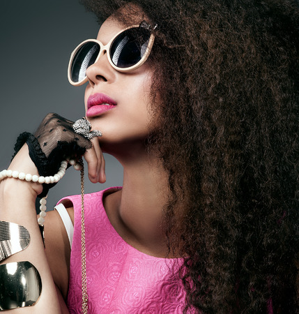 Fashion Foto der schönen eleganten afrikanischen amerikanischen Frau. Mädchen posiert mit viel Schmuck, tragen modische Sonnenbrille. Mädchen mit den langen lockigen gesundes Haar. Beauty portrait. Studio shot. Lizenzfreie Bilder