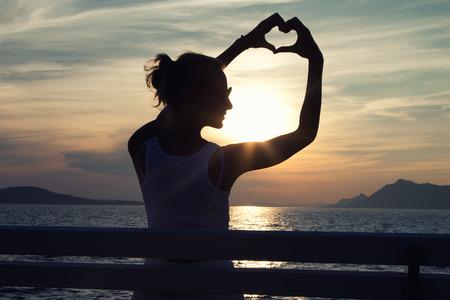 Konzeptionelle Foto der schönen jungen Frau, die Hände in Herzform Umrahmung Sonne bei Sonnenuntergang setzen. Sommer-Foto. Draussen.
