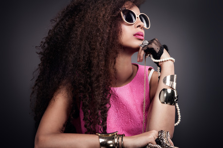 Fashion photo of beautiful elegant african american woman. Girl posing with a lot of jewelry, wearing fashionable sunglasses. Girl with long curly healthy hair. Beauty portrait. Studio shot.