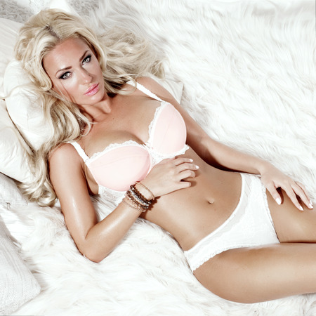 nude bride: Sensual blonde beauty lying in bed, relaxing. Beautiful woman in sexy lingerie. Stock Photo
