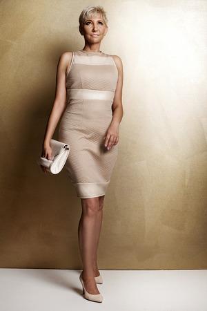 mujer rubia desnuda: Elegante y bella mujer rubia posando en estudio, vistiendo traje de moda y bolsa. Señora con el pelo corto. Foto de archivo