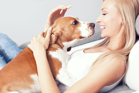 Beautiful young blonde woman playing with her dog at home, smiling. Happiness. Фото со стока