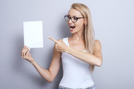 rubia: joven rubia mujer con tablero vacío blanco sonriente. Chica de moda el uso de anteojos. estudio de disparo.