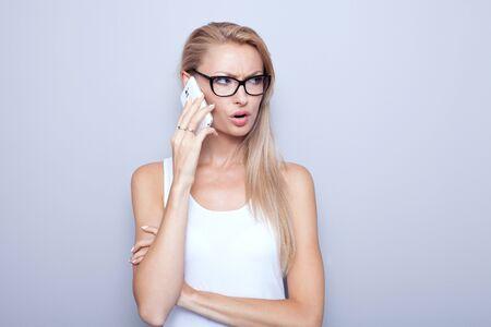 shocked: Young beautiful blonde woman talking by mobile phone. Attractive girl wearing eyeglasses. Grey wall. Stock Photo