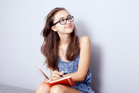 learning by doing: Young teenage girl doing homework, learning. Photo at home.