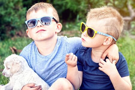 outdoor photo: Two boys having fun with puppies. Summer time. Outdoor photo.