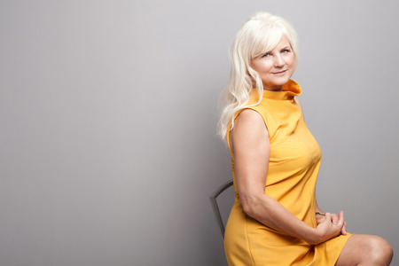 hair studio: Portrait of beautiful fashionable senior woman with long grey hair. Lady wearing yellow dress, looking at camera. Studio shot.