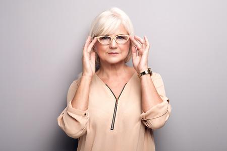 Portrait of cheerful senior woman wearing eyeglasses, looking at camera. Lady with grey hair. Studio shot.