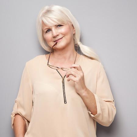 Schöne attraktive ältere Frau, posiert im Studio, mit Brille in der Hand.
