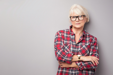 stylish hair: Fashionable senior woman with grey hair posing in studio, looking at camera. Casual look.