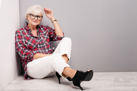 woman posing: Fashionable senior woman with grey hair posing in studio, looking at camera. Casual look.