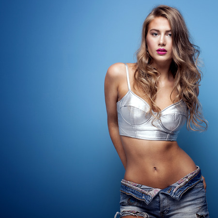 Sexy beautiful young woman posing on blue background, looking at camera. Girl in short jeans and silver fashionable top. Studio shot. Standard-Bild