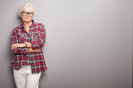 stylish women: Fashionable senior woman with grey hair posing in studio, looking at camera. Casual look.
