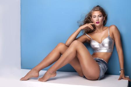 rubia ojos azules: Sexy hermosa mujer joven posando sobre fondo azul, mirando a la c�mara. Muchacha en pantalones vaqueros cortos y plata principio de moda. Estudio de disparo.