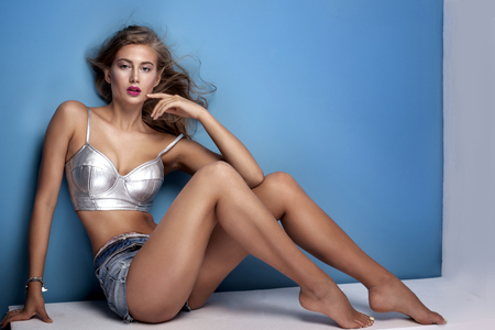 femme brune sexy: Sexy belle jeune femme posant sur fond bleu, regardant la cam�ra. Fille en jeans courts et d'argent sup�rieure � la mode. Studio, coup.