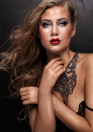 nude fashion model: Beauty portrait of sensual woman with long curly hair and glamour makeup. Girl wearing necklace. Red lips. Studio shot. Closeup photo. Stock Photo