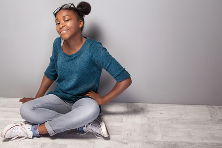 sit: Young beautiful teenage girl sitting on the floor. Girl with eyeglasses on head looking at camera, smiling.