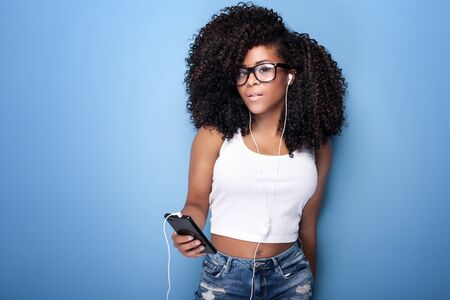 afro american nude: Beautiful young woman with afro listening to music from mobile phone. Studio shot. Blue background.