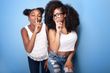 woman posing: Two beautiful african american girls smiling, looking at camera. Sisters posing on blue background. Studio shot. Stock Photo