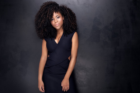 long curly hair: Young beautiful african american girl posing in elegant dress, looking at camera. Girl with afro. Studio shot.