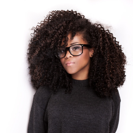 long curly hair: Portrait of beautiful african american young girl. Girl with afro and eyeglasses.