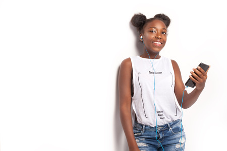 girl in jeans: Young smiling teenage girl listening to music from mobile phone. African american girl. Studio shot.