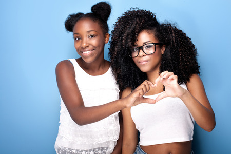 woman pose: Two beautiful african american girls smiling, looking at camera. Sisters posing on blue background. Studio shot. Stock Photo
